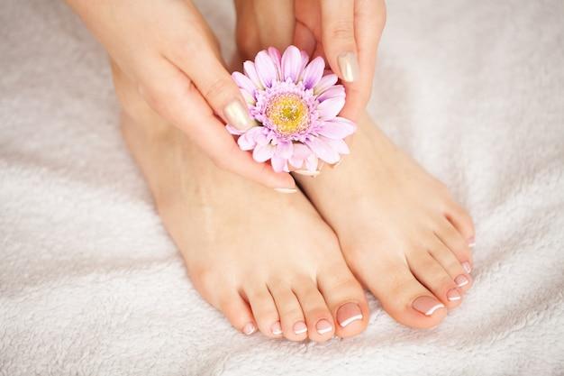 Pedicure francês da mulher. feche acima das mãos da mulher que tocam nas pernas longas, pele macia. depilação