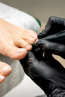 Pedicure mestre remove cutícula dos dedos dos pés de uma mulher em um salão de beleza