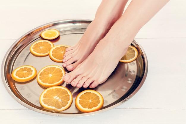 Pedicure no salão spa com fatias de laranjas em um fundo branco de madeira
