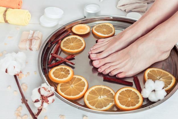 Pedicure no salão spa com laranjas fatiadas, canela e algodão