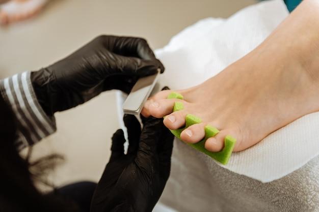 Pedicure para cliente. quiropodista profissional experiente que faz luvas pretas fazendo pedicure para sua cliente