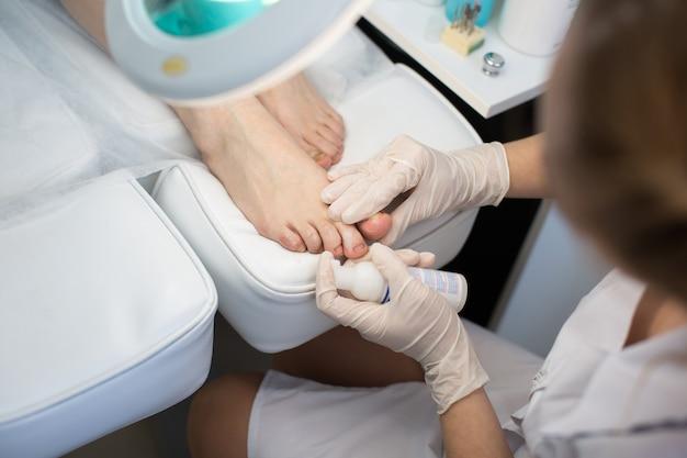 Pedicure removedor de pele morta pé grosa mulher em salão de beleza. aplicação do creme