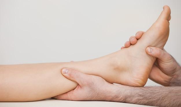 Pedicure segurando o tornozelo de um paciente
