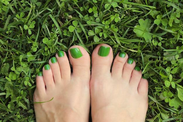 Pedicure verde nos pés da mulher em fundo de grama