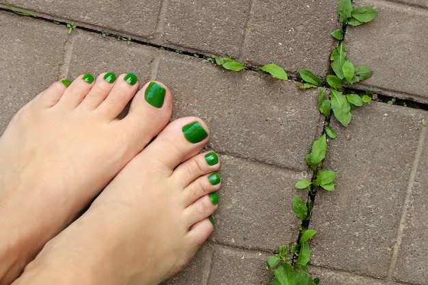 Pedicure verde nos pés da mulher no chão de concreto com plantas crescendo nele