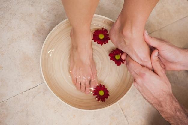 Pedicurista lavando os pés de um cliente