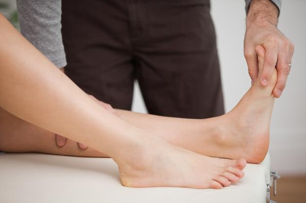 Pedicuro tocando o pé de um paciente