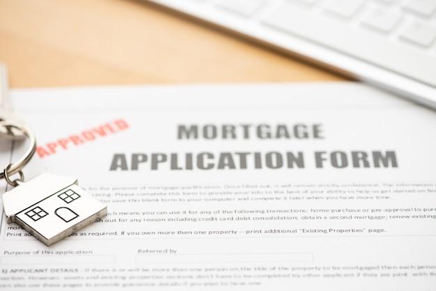 Pedido aprovado de contrato de empréstimo hipotecário com chaveiro em forma de casa close-up