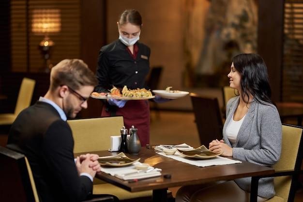 Pedido de comida sendo entregue a dois visitantes do restaurante