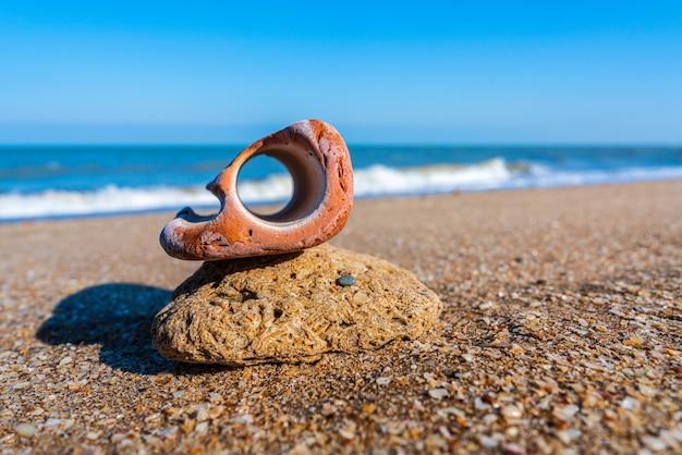 Pedra bizarra com buraco na praia
