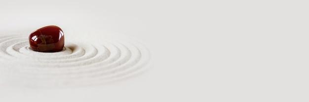 Pedra brilhante na areia. cena de fundo do jardim japonês zen. banner horizontal