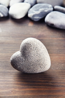 Pedra cinza em forma de coração, na mesa de madeira