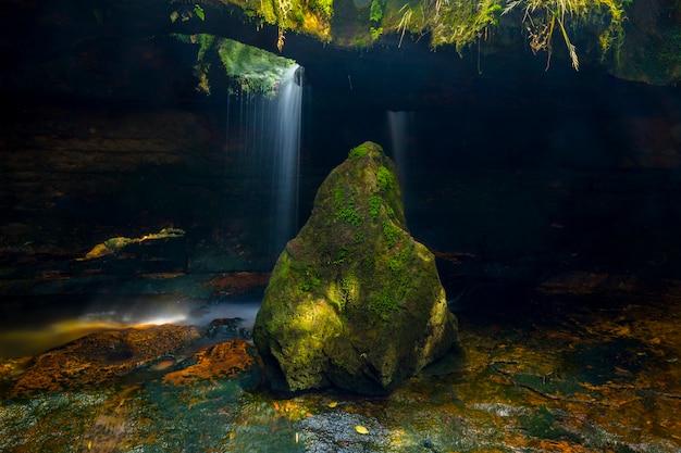 Pedra coberta de musgo com caverna ao fundo com cascata