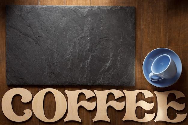 Pedra de ardósia preta e letras de café na superfície de madeira
