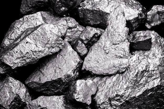 Pedra de manganês, manganês ou magnésio é um elemento químico, está na fabricação de ligas metálicas. minério prateado, uso industrial. minério em fundo preto isolado.