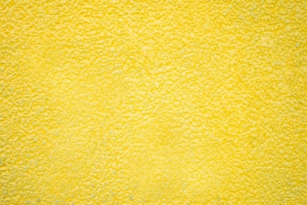 Pedra do cascalho pintado fundo amarelo textura.