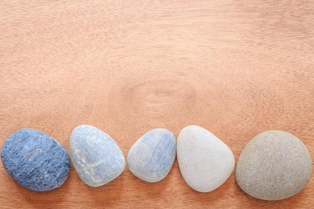 Pedra do zen e dos termas no de madeira liso com área de espaço da cópia.