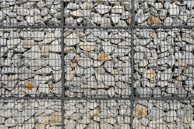 Pedra e seixos na parede de malha de arame.