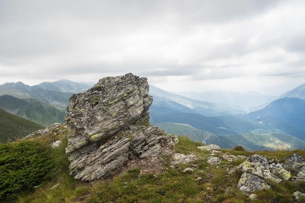 Pedra em uma colina coberta de vegetação com montanhas rochosas sob um céu nublado