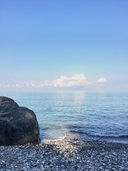 Pedra enorme em uma praia de calhau