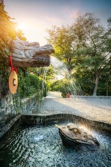 Pedra esculpindo dragão pulverizando paisagem aquática