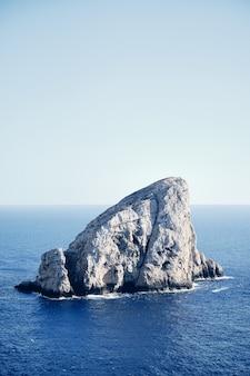 Pedra grande no meio do mar com um céu azul