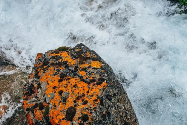 Pedra laranja grande com musgo e líquen no riffle de água do rio da montanha. fluxo de água poderosa do riacho de montanha. natureza textura rápido fluxo rápido de riacho de montanha. close-up de pedra musgosa