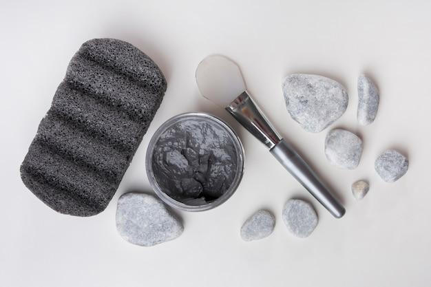 Pedra pomes; pedras de spa; máscara de argila e pincel em fundo branco