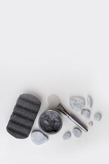 Pedra pomes; pedras de spa; máscara de argila e pincel isolado no pano de fundo branco