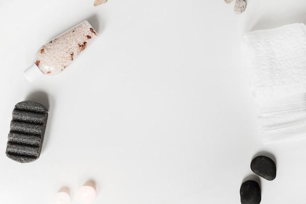 Pedra pomes; sal de ervas; pedra de spa; velas e toalha no fundo branco