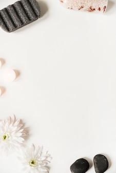 Pedra pomes; sal; último; velas e flores sobre fundo branco