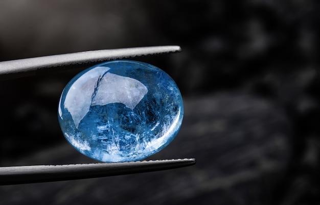 Pedra preciosa de safira azul índigo com fundo de rocha escura.