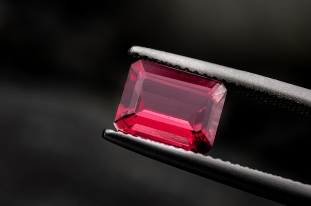 Pedra preciosa rubi vermelha com fundo preto escuro.