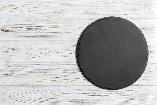 Pedra preta ardósia redonda sobre fundo de madeira, vista de cima, copie o espaço