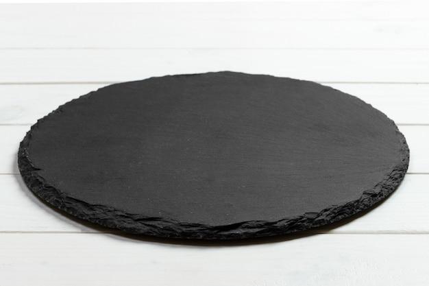 Pedra redonda de ardósia preta sobre fundo de madeira