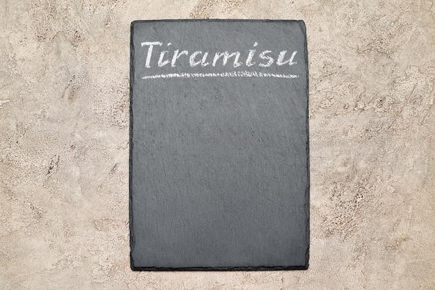 Pedra servindo quadro de menu com placa de tiramisu escrita à mão em giz