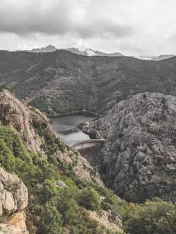Pedras altas, cobertas de vegetação e vista para um lago sob um céu nublado