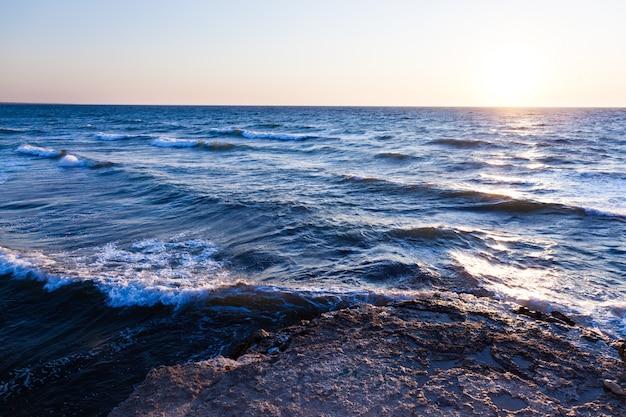 Pedras azuis bonitas do por do sol e da água sobre o mar negro
