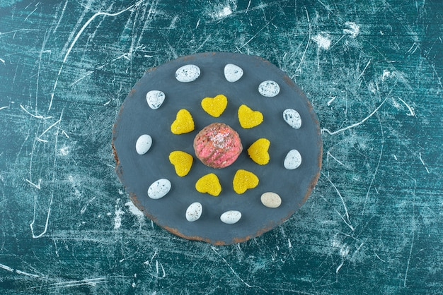 Pedras de chocolate e marmeladas em torno de um biscoito coberto de chocolate em um quadro azul.
