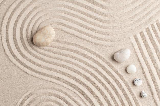 Pedras de mármore zen e fundo de areia no conceito de paz
