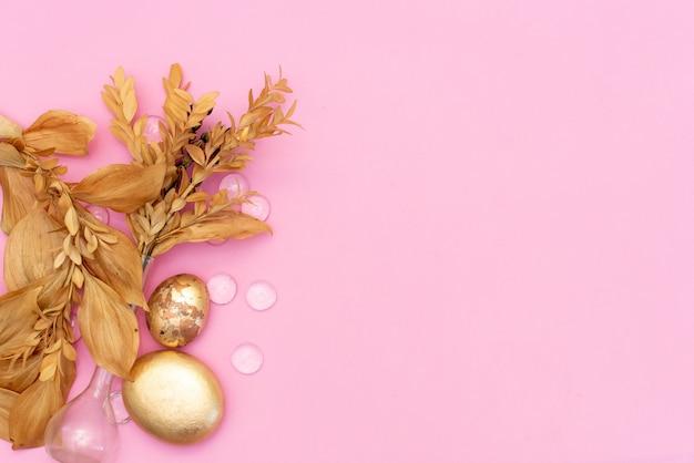 Pedras de ouro e flores secas em um fundo rosa com copyspace
