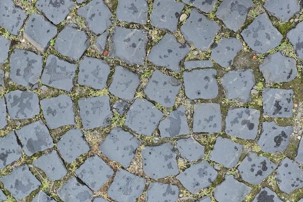 Pedras de pavimentação redondas velhas de pedras cinzentas