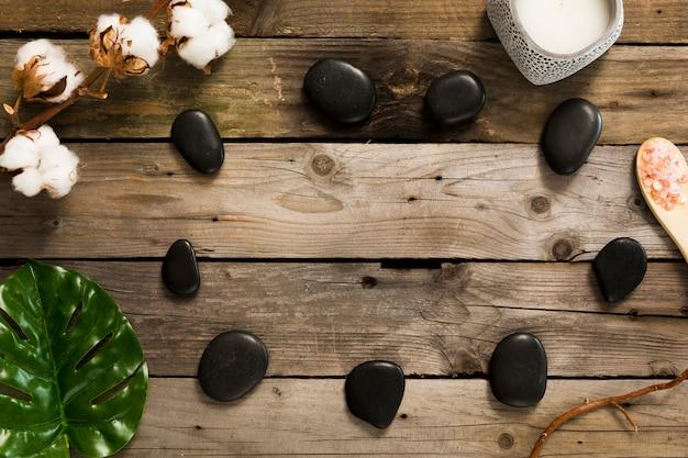 Pedras de spa com flores de algodão e folhas verdes na mesa de madeira