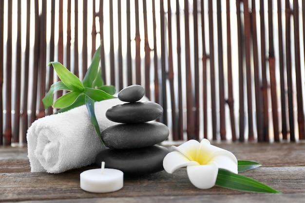 Pedras de spa com toalha, bambu, vela e flor tropical em superfície de madeira