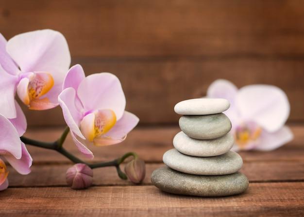 Pedras de spa e flores de orquídea rosa