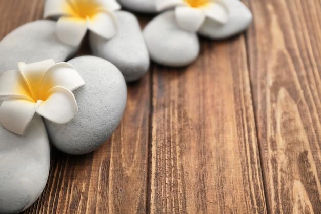 Pedras de spa e lindas flores na parede de madeira