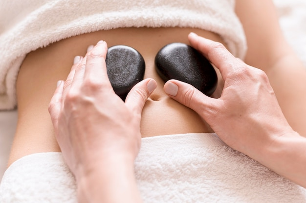 Pedras de spa no abdômen do cliente