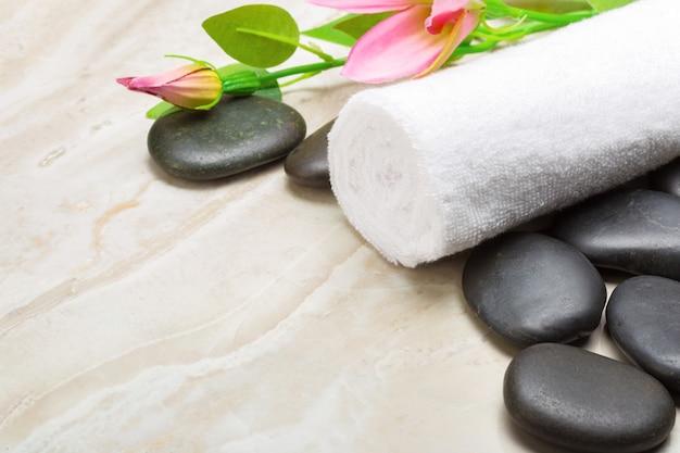 Pedras de spa, toalha e flores sobre fundo de madeira
