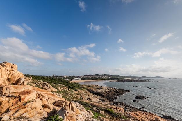 Pedras de várias formas intemperizadas pelo mar sob o céu azul