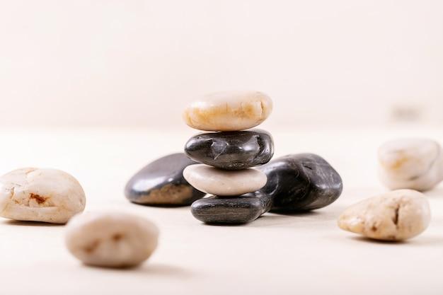 Pedras decorativas brancas e pretas e seixos sobre fundo cinza de madeira